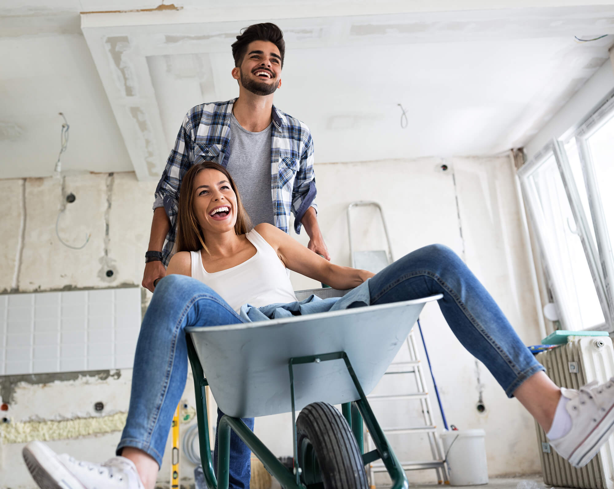 Man pushing women in wheelbarrow for fun in renovated house project