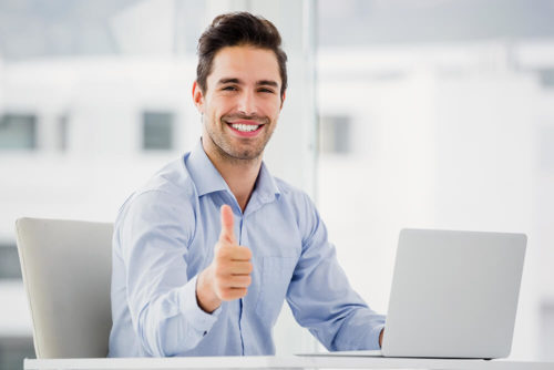 Man smiling and giving a thumbs up while working on a computer