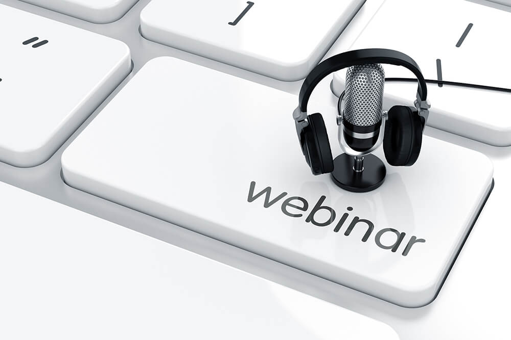 Small microphone with headphones on top of a keyboard button that says 'Webinar'